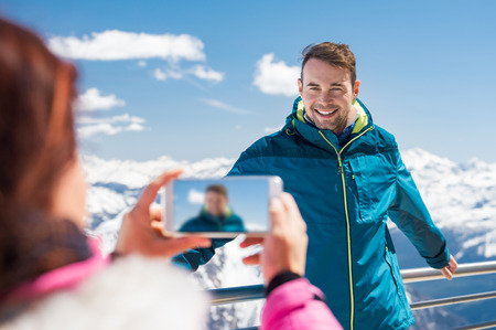 Young man posing for photo with mountains covered by snow. Stock Photo