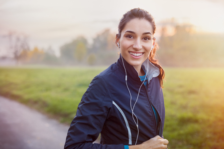 Young beautiful woman listening music at park while running. Banque d'images