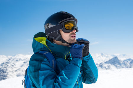 Man skier wearing helmet and ski mask on snowy mountain.