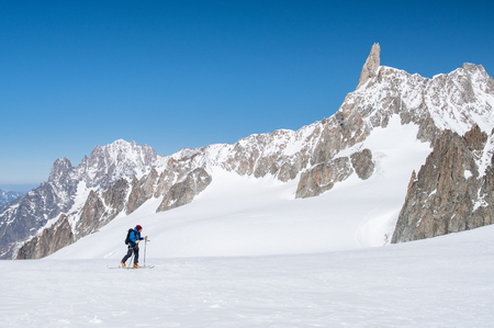 Mountaineer exploring a glacier with skis in winter expedition on Alps.