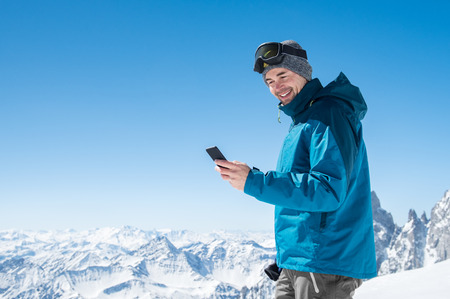 Happy man using smartphone in snowy mountains after skiing.