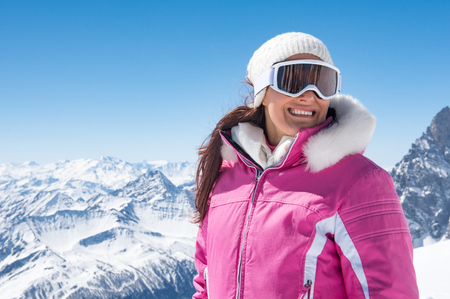 Happy woman with mask for snowboarding looking away with mountains covered by snow in background.