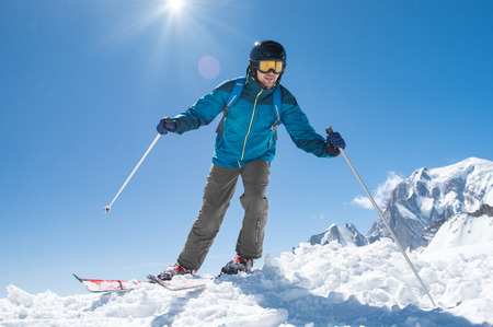 Happy man in winter clothing skiing on mountain slope. Stock Photo