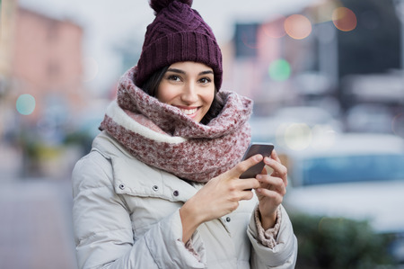 cold: Happy young woman holding smartphone and looking at camera.