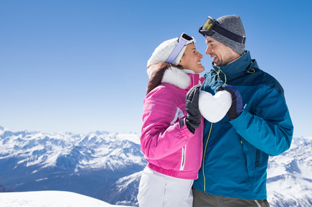 Young couple looking at each other and holding snow heart.