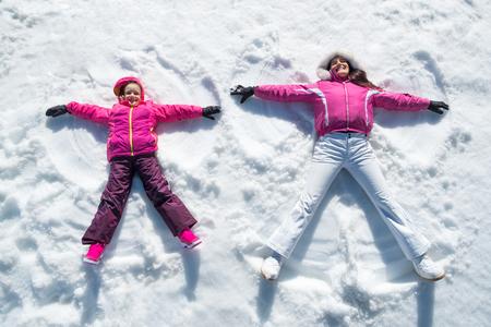 かわいい娘と遊んで、雪の中で横になっている母の高角度のビュー。