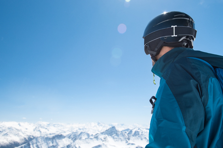 Rear view of man in snowy mountain wearing helmet and looking the snowy landscape.