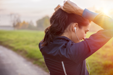 Woman tying hair in ponytail getting ready for exercising at sunset. Stock Photo