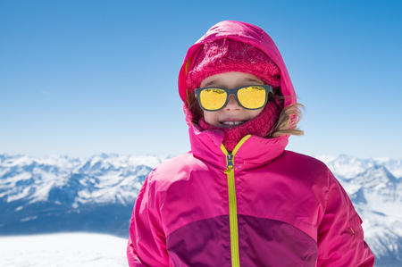 Portrait of happy little girl with sunglasses enjoy ski outdoor. Stock fotó