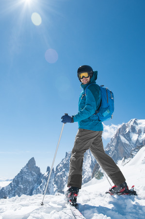 Skier standing alone and looking at camera with snowy mountain in background.