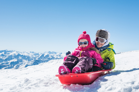 Happy little brother and cute sister enjoying sleigh ride.