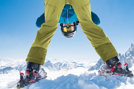 Sporty man bending down playing in snow with ski. Man having fun while skiing on snowy mountain. Happy skier in winter clothing looking at camera between legs.