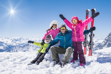 Laughing family in winter vacation with ski sport on snowy mountains.