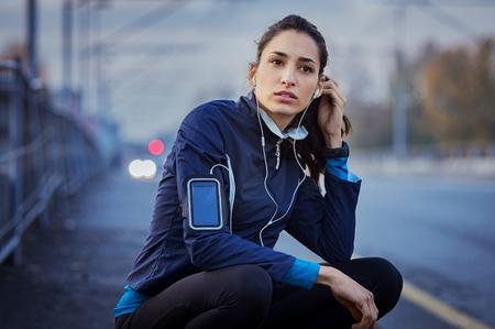 조깅 운동 중에 음악을 듣고있는 동안 도로에 앉아 여자 선수.
