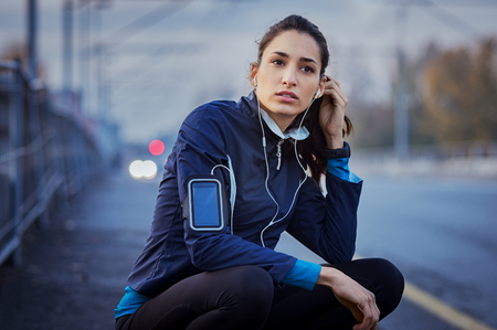 Woman athlete sitting on road while listening to music during jogging exercise. Archivio Fotografico