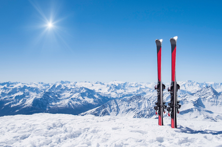 Red skis standing in snow with winter mountains in background.