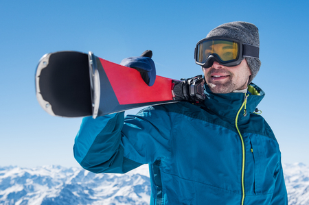 Happy skier holding a pair of skis and looking at the snowy mountains.