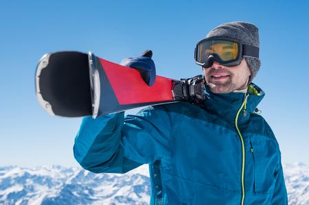 행복 스키어 스키의 쌍을 들고와 눈 덮인 산에서 찾고.