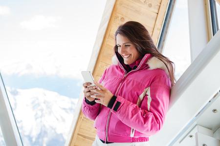 冬の間に山で移動しながら携帯電話を使用して暖かいジャケットで、若い女性。