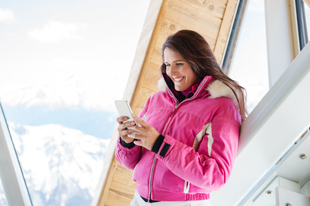 Young woman in warm jacket using mobile phone while traveling in mountain during winter. Banco de Imagens