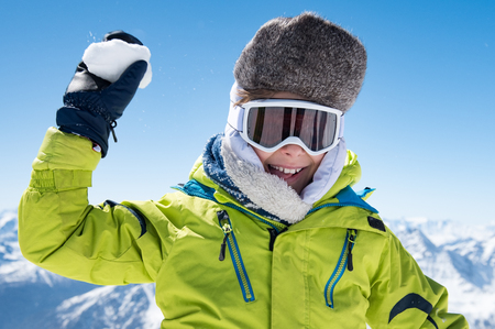 Child in yellow jacket and ski glasses playing snowballs.