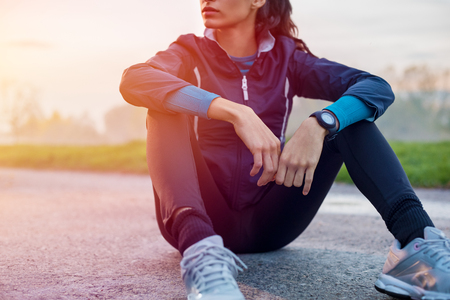 Young athlete sitting on ground to relax after jogging at sunset.