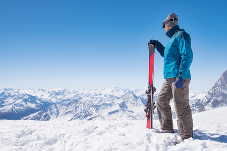 Skier holding ski and looking at beautiful snow covered mountains. Stock Photo