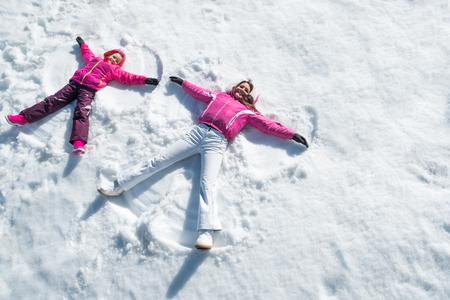 陽気な母と娘の雪の中でカメラを見ながら楽しんでいます。