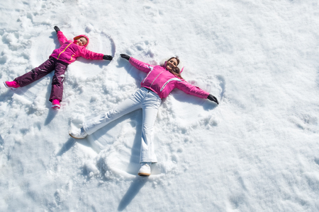 Cheerful mother and daughter enjoying in snow while looking at camera. Standard-Bild