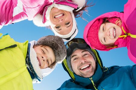 Smiling family with heads in a circle looking at camera in winter holiday. photo
