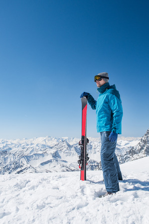 Skier holding a pair of skis and looking at the snowy mountains. photo