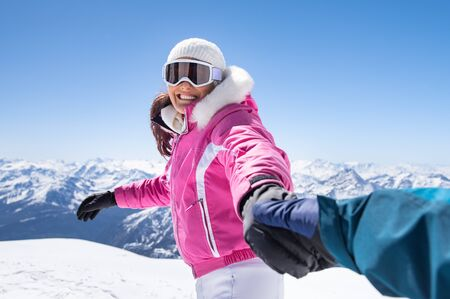 Cheerful young woman in pink winter wear holding boyfriend hand. photo
