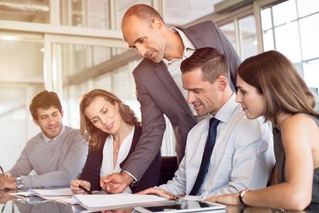 Teamleider wijzend op rapport tijdens ontmoeting met zijn collega's. Commercieel team dat in modern bureau samenwerkt. Jonge meningen van bureau die nieuwe ideeën bespreken voor marketing met werkgever.