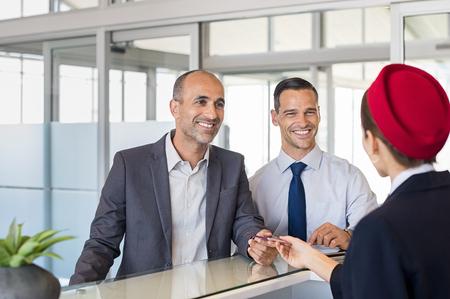 Rijpe zakenman die paspoort en kaartje geven aan personeel bij luchthavencontroleteller. Zakenman die bij luchthaven met zijn collega incheckt. Gelukkige glimlachende mens die paspoort overhandigt aan stewardess. Stockfoto