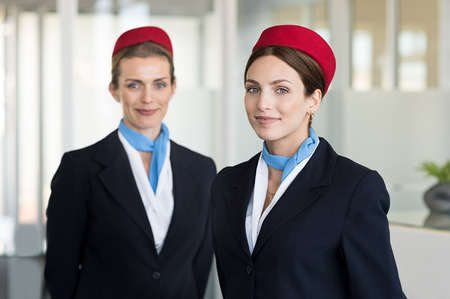 Two airhostess in uniform at airport looking at camera. Flight attendants standing together in blue and red uniform. Portrait of smiling young hostess ready for flight.