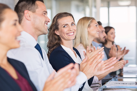 Businessmen and business women sitting in a row and applauding at meeting. Successful businesspeople clapping hands after presentation. Happy group of business people sitting in a row at conference.