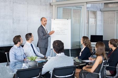 Homme d'affaires mature confiant donnant une présentation à son équipe dans les bureaux modernes. Brief d'affaires avec des objectifs annuels avec les employés. Homme de leadership formant des hommes d'affaires et des femmes d'affaires dans la salle de conférence.