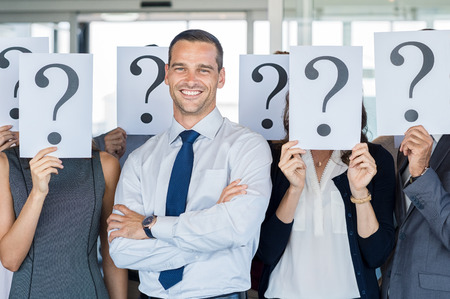 questions: Happy businessman standing out of the crowd. Smiling business man standing with crossed arms while team hiding their faces with question mark sign. Business man find his own career path.