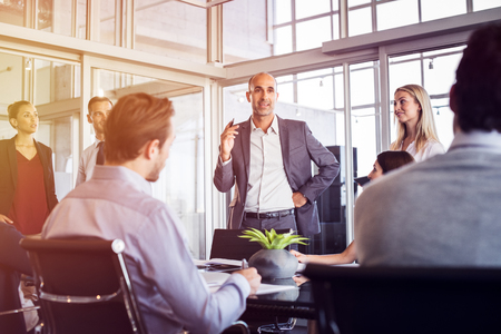 年配の男性は、オフィスでのミーティングで社員に話しています。マーケティング チームは会議中にマネージャーと新しいアイデアを議論します。