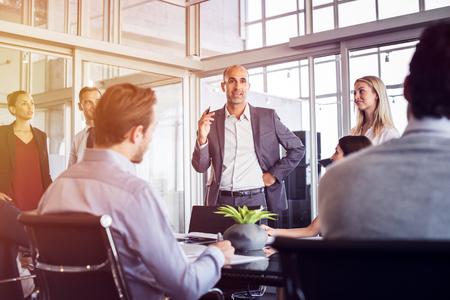 Hogere mens die aan werknemers in bureaubeeting spreekt. Marketingteam nieuwe ideeën bespreken met manager tijdens een conferentie. Senior leiderschap training van toekomstige zakenlieden en zakenvrouwen.