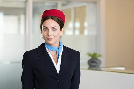 Portret van jonge luchtstewardess die zich bij luchthaven bevinden en camera bekijken. Portret van vluchtassistent in eenvormige status dichtbij controleteller. Gelukkige agent die de stewardessuniform op luchthaven draagt.