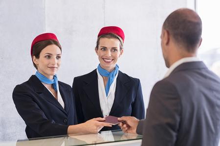 Vrouw in checkin teller met paspoort voor verificatie van passagier man. Gelukkige lachende gastvrouw bij inchecken met haar collega. Zakenman op zakenreis op luchthaven. Stockfoto