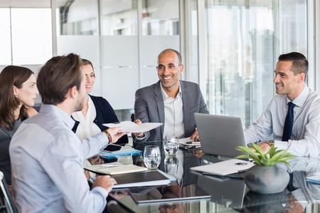 Hombre de negocios que pasa sobre los documentos al líder durante la reunión. Hombre de negocios que pasa el acuerdo necesario para el socio de negocios en la sala de conferencias. Grupo de empresarios y empresarias trabajando juntos. Foto de archivo