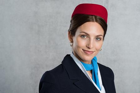 Glimlachende luchtstewardess die camera bekijkt. Succesvolle vluchtassistent die eenvormig draagt ??die over grijze achtergrond wordt geïsoleerd. Jonge stewardess camera kijken en glimlachen. Stockfoto