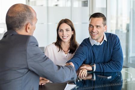 사무실에서 젊은 부부와 함께 악수하는 사업가. 은행 에이전트와 그의 클라이언트 회의실에서 악수. 해피 몇 웃는 자신의 개인 재무 고문과 인감.