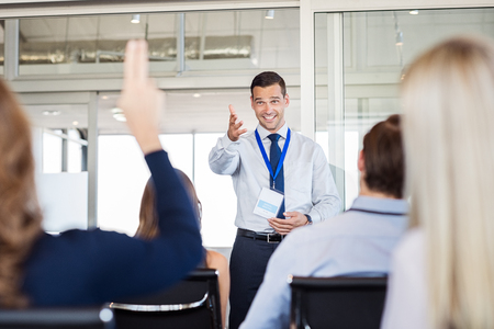 questions: Businessman in seminar pointing towards woman raising hand to say a question. Human resource manager training new company employees. Businesswoman raising hand at conference to answer a question. Stock Photo