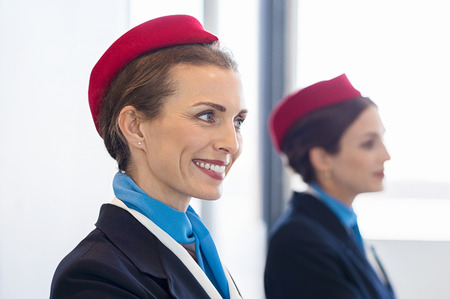 Cheerful hostess smiling at airport check in. Portrait of a happy mid woman in uniform at airport looking away. Close up face of confident flight assistant working at airport.