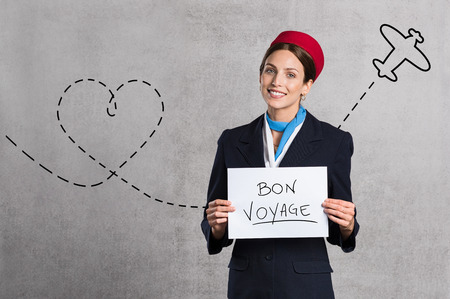Young air hostess holding Bon Voyage sign isolated on grey background. Flight assistant holding sign with airplane route in the background. Woman stewardess with board and copy space. Stock Photo