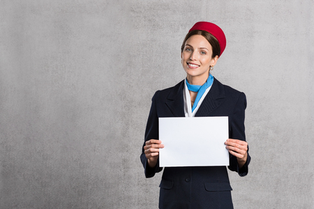 board: Young air hostess holding white placard isolated on grey background. Flight assistant holding blank sign and looking at camera. Woman stewardess with empty board and copy space.