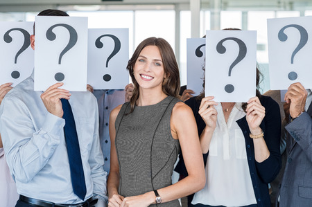 questions: Businesswoman standing out of the crowd. Happy smiling business woman with other people hiding their faces behind a question mark sign. Successful businesswoman find her job and career path. Stock Photo